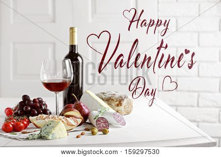 Text HAPPY VALENTINE'S DAY. Glass of red wine and food on table.