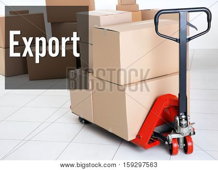 Word EXPORT on background. Hand palette truck with cardboard boxes at storehouse. Wholesale and logistics concept.