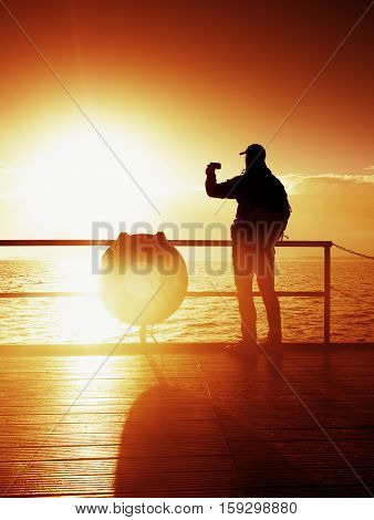 Tourist Photograph  On Sea Mole. Hiker Take Photos Of Morning Sea. Autumn Fog. Tourist On Wooden Boa