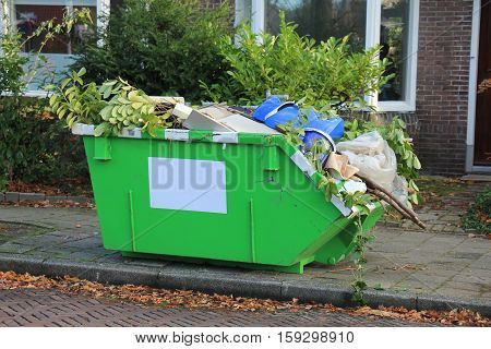 Loaded dumpster near a construction site home renovation