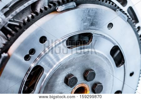 Steel flywheel mounted on the engine. Abstract industrial background.