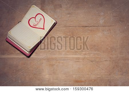 pocket book with love symbol; opened notebook on wooden background and with picture of heart on page;