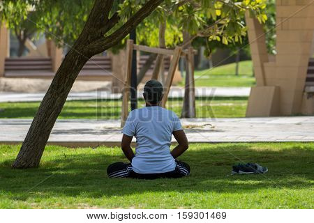 A man practicing yoga in the shade of a tree in a park in Bahrain