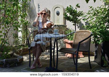 Woman in elegant summer clothes with adorable dog - Cavalier King Charles Spaniel - in garden shadows