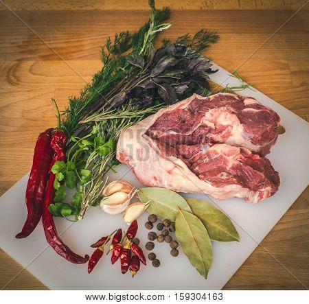 Fresh raw lamb on wooden cutting board, spices and herbs. Whole uncooked lamb prepare for cooking. Large piece of fresh leg lamb.