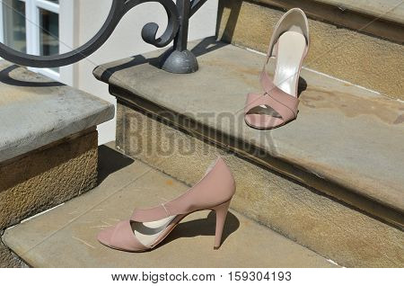 Pair of nude look elegant stiletto sandals on stone stairs