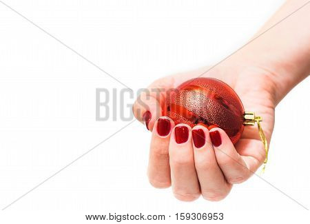 Red round christmas ball in female hand isolated on white background. Close up of young woman hand with beautiful professional red manicure. Christmas celebration concept.