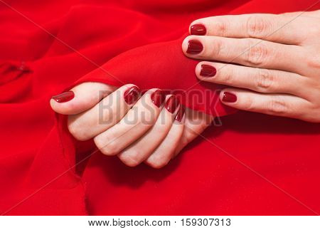 Close up of young caucasian female hands with professional red manicure with glittering sparkles at red fabric background. Modern festive gel polish with base coat first and top cure with UV LED lamp