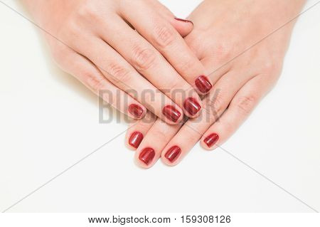 Close up of caucasian female hands with professional red manicure with glittering sparkles isolated on white background. Modern festive gel polish with base coat first and top cure with UV or LED lamp
