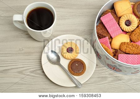 Cup of coffee with a tin filled with biscuits