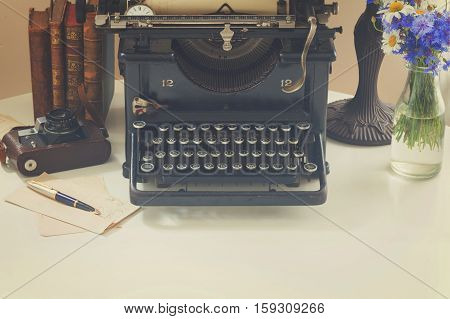 black vintage typewriter with books on white wooden table with copy space, retro toned