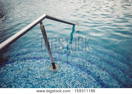 detail of thermal swimming pool tiled stairs down water and metal handle