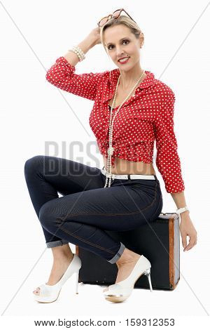 fashion blonde woman with jeans sitting on a suitcase isolated on white background