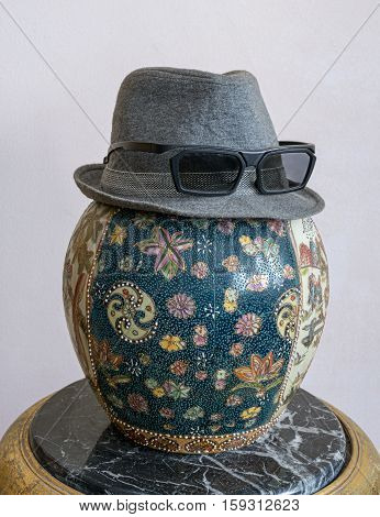 Gray trilby hat wearing sunglasses over antique decorated Chinese ceramic jar vase over antique black marble table
