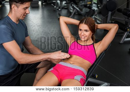 happy cutie athletic girl , with instructor execute abdominal exercises and smile, in sport-hall