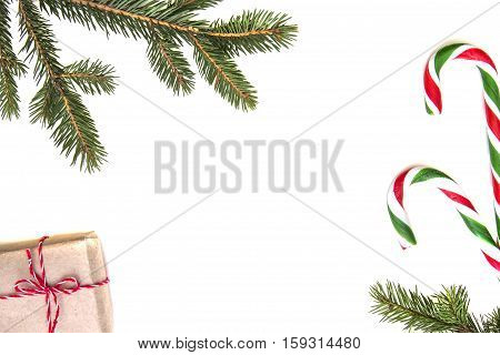 Christmas composition. Green Christmas tree twings, gifts and candy canes on white background. Top view, flat lay. Copy space for text. Winter holidays concept