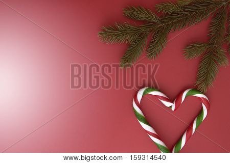 Christmas background with green tree twings and candy canes on red. Top view, flat lay. Copy space for text. Winter holidays concept