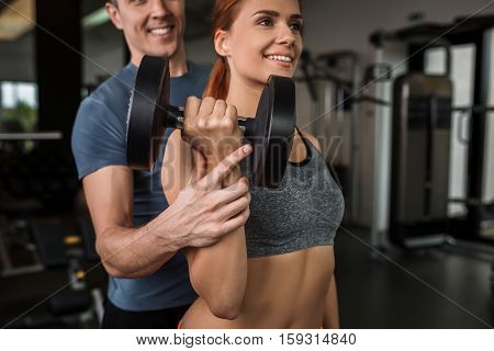 happy cutie athletic girl , with instructor execute exercises with dumbbells and smile, in sport-hall