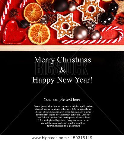 Christmas greeting card with copyspace, made like frame with black place for text or wishes. Sweets, cinnamon, dried oranges, toys, ginger snaps and spices. Samle text for example.