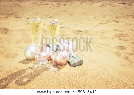 Two glasses of christmas champagne with christmas gifts and decorations on beach sand, retro toned