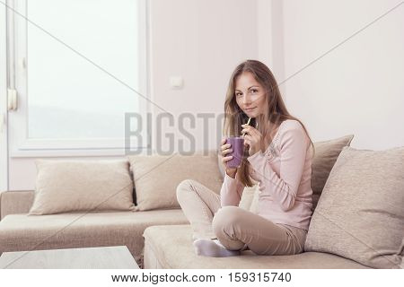 Beautiful girl sitting on a living room couch and drinking a fruit mix smoothie. Lens flare effect on the window
