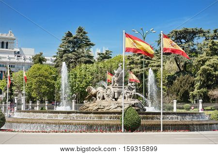 Cibeles Fountain and spanish flags famous landmark in Madrid Spain.