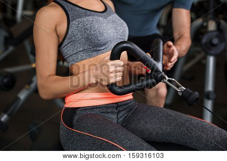 happy cutie athletic girl , with instructor execute exercises and smile, in sport-hall