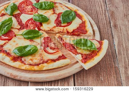 Pizza Margherita with tomatoes mozzarella and basil on a wooden background сlose up.