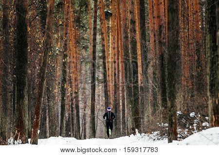 General plan athlete runner running a marathon winter on a snowy trail in pine forest