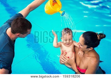 Baby swimming lessons - baby mother and instructor having fun in the swimming pool