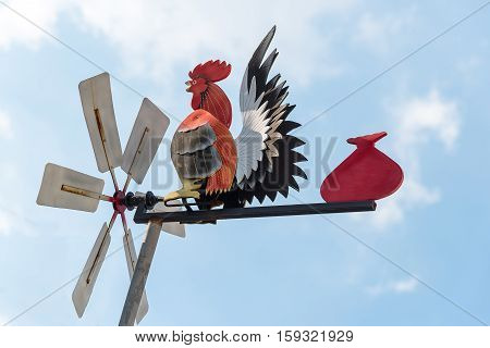 Hen-shaped Weather Vane Over The Top Of A Pointy-roofed House Against Cloudy Blue Sky.