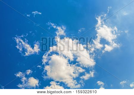 Blue sky with white fluffy cumuli clouds.
