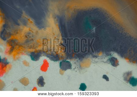 overflowing bright orange and dark blue paint on paper. Shabby style abstract faded background. Mixing paints close-up