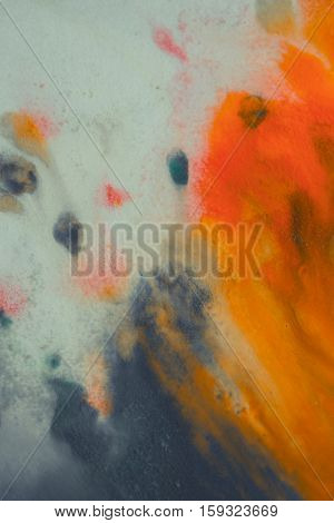 overflowing bright orange and dark blue paint on paper. Shabby style abstract faded background. Mixing paints close-up.