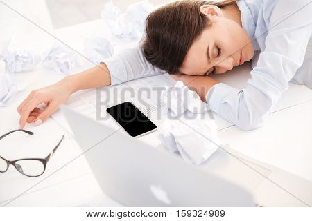 Photo of tired woman at office desk sleeping with eyes closed, sleep deprivation and stressful life concept