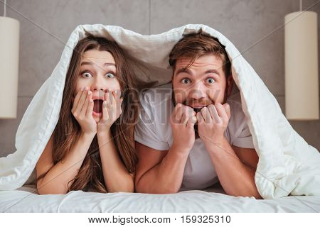 Surprised young loving couple looking at camera while lying in bed under blanket and holding their face with hands.