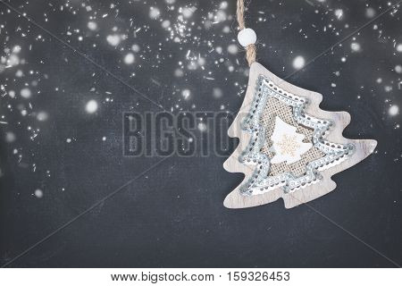 Decorative christmas tree on black wooden background with snow