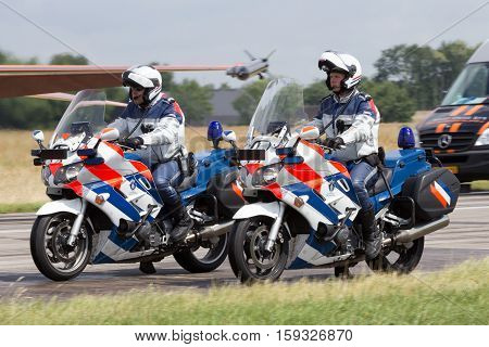 VOLKEL NETHERLANDS - JUN 15 2013: Dutch military police (Marechaussee) officers patrolling on their bike at the Royal Netherlands Air Force Open Day.