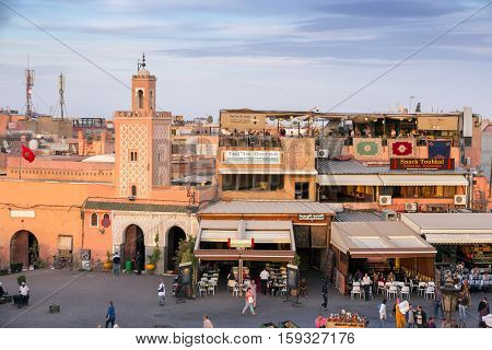 MARRAKECH MOROCCO - APR 29 2016: Mosque and restaurants with tourists on the Djemaa-el-Fna square in Marrakech