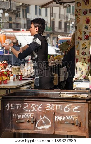 Verona Italy 27 October 2013 - female chestnut seller at work. Text in italian indicates chestnuts price