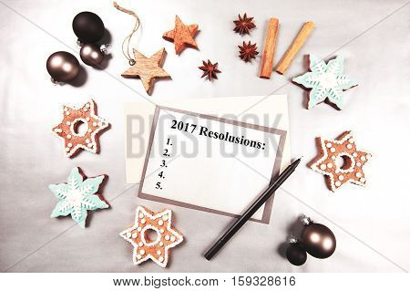 List of New Year resolutions made in flat lay style. Christmas and new year holiday frame, made with sweets, stars, cup of coffee, heart, cinnamon, beautiful ginger snaps - snowflakes and spices on silver background.