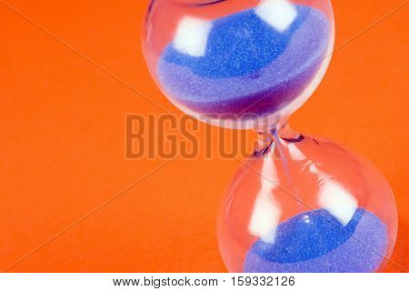 Blue sand clock on orange background passing time concept.