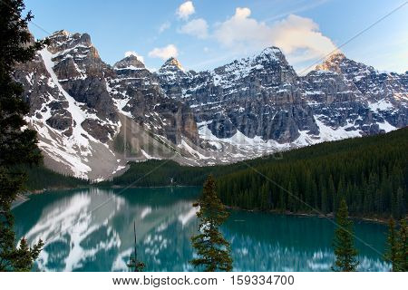 Moraine Lake, Alberta, Canada. The setting sun lights up the tops of the mountain peaks behind like glowing torches as the cloud wisps double as smoke. The snow covered slopes are reflected in the azure glass-like lake water