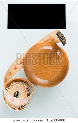 Yo-yo effect in diet concept. Wooden yoyo with centimeter measure. Bathroom weight scale with black display screen. Flat lay top view. Vertical orientation.