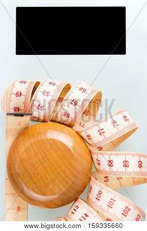 Yo-yo effect in diet concept. Wooden yoyo with centimeter measure. Bathroom weight scale with black screen display. Vertical orientation.