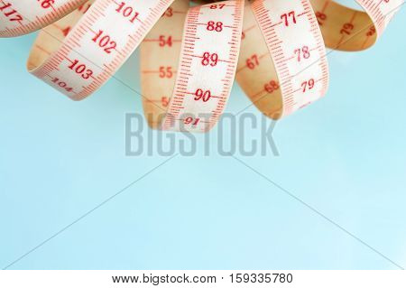Yo-yo effect in diet concept. Centimeter tape measure. Blue pastel background. Copy space on the bottom.