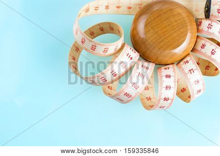 Yo-yo effect in diet concept. Wooden yoyo with centimeter measure. Blue pastel background. Copy space in the bottom left corner.