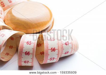 Yo-yo effect in diet concept. Wooden yoyo with centimeter measure. Isolated on white background. Copy space on the right.