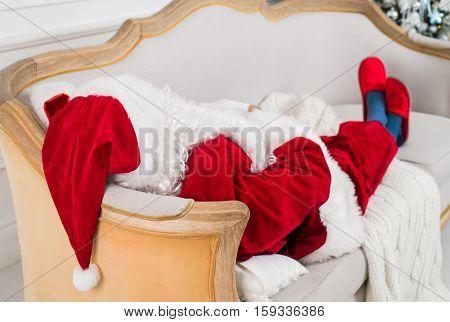 Santa Claus resting on a sofa at home. Funny Santa lying, christmas pause