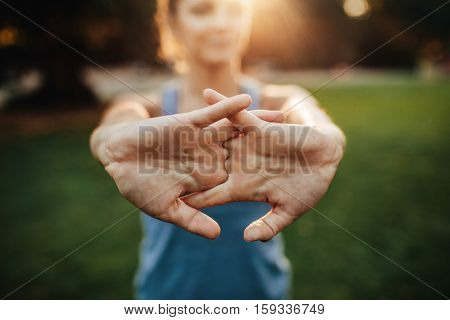 Young woman stretching arms outdoors. Fitness female doing warmup exercise at the park focus on hands.